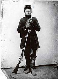 Black and white photograph of Private George Fehrenbacher of Company F standing in his Civil War uniform holding his Springfield rifle musket with bayonet